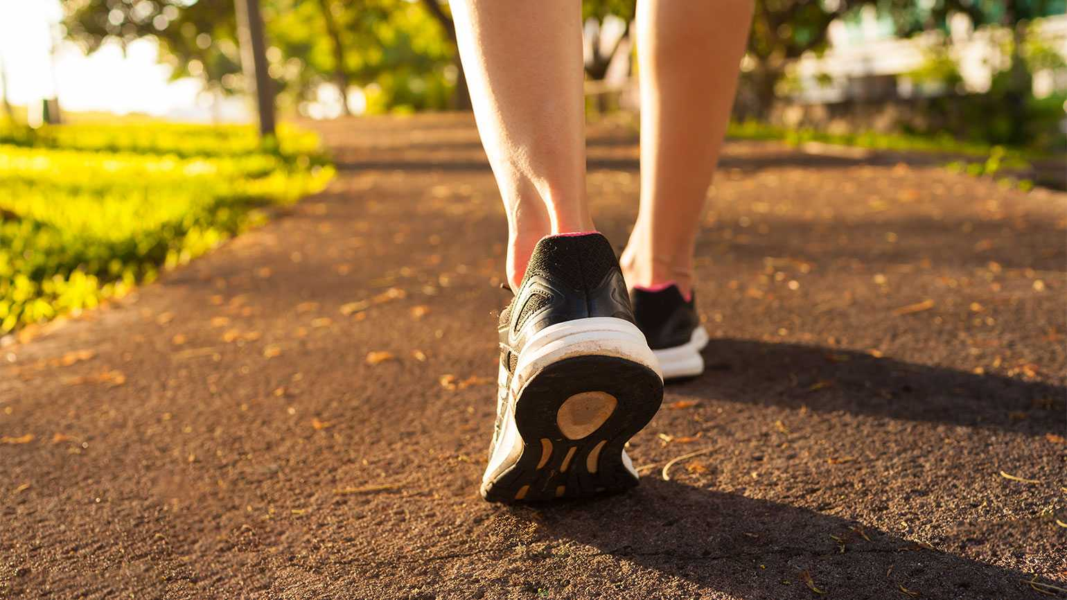A close-up of a woman's sneakers as she takes a healthy walk in the park