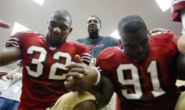 Smith prays with Kevan Barlow (left) and Anthony Adams in the locker room before a game against the Indianapolis Colts.