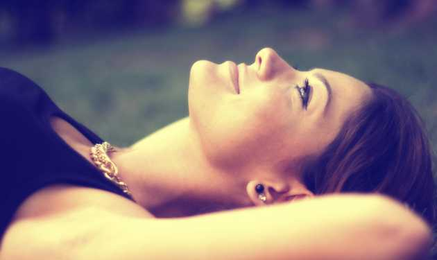 a woman lies in the grass witnessing God's glory in creation