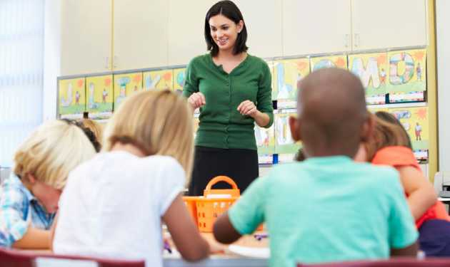A smiling teacher addresses her young students in the classroom
