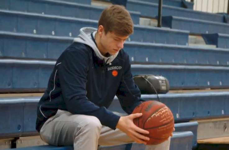Teen sits on the bleachers holding a signed basketball.