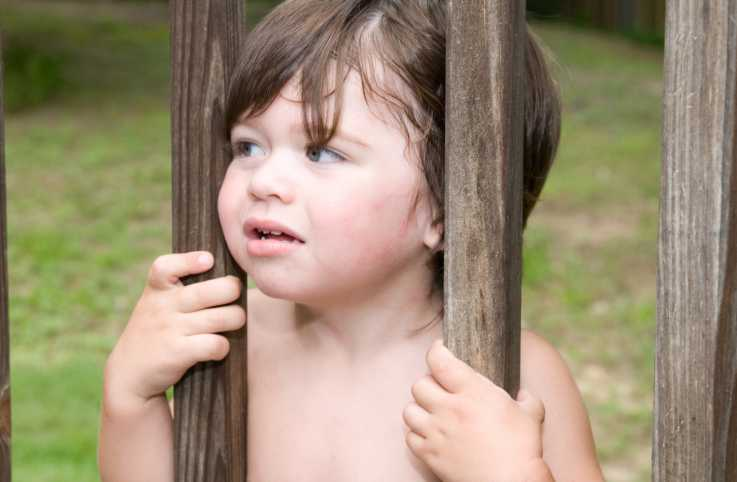 Child stuck behind fence.