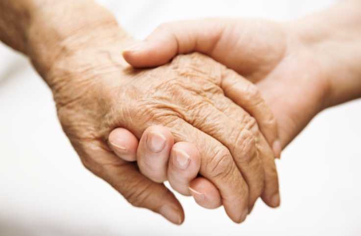 A caregiver holding the hand of a loved one.