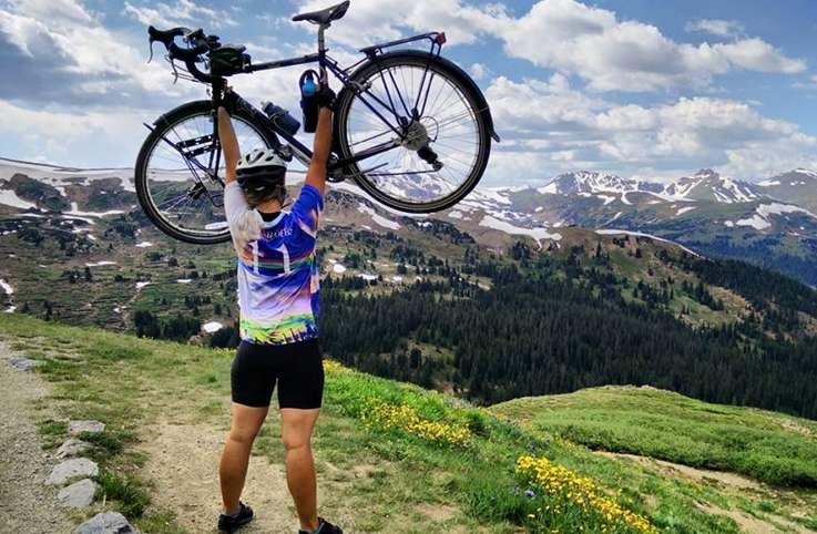 Deborah Kraft celebrates crossing the Continental Divide on her bike journey from Maine to the Oregon Coast