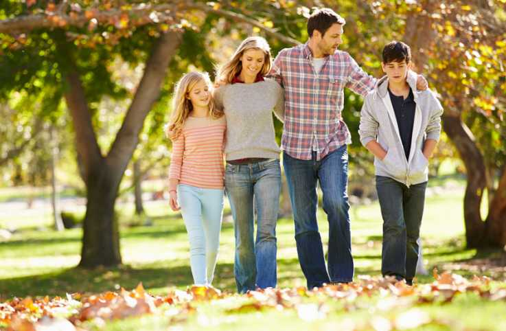 A mother, father, daughter and son go for a stroll on a sunny autumn day
