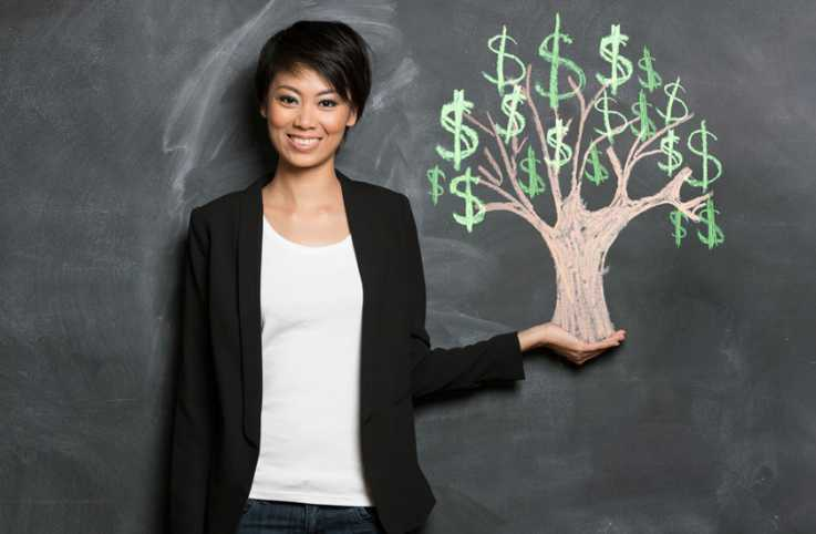 A smiling woman stands next to a chalkboard illustration of a money tree