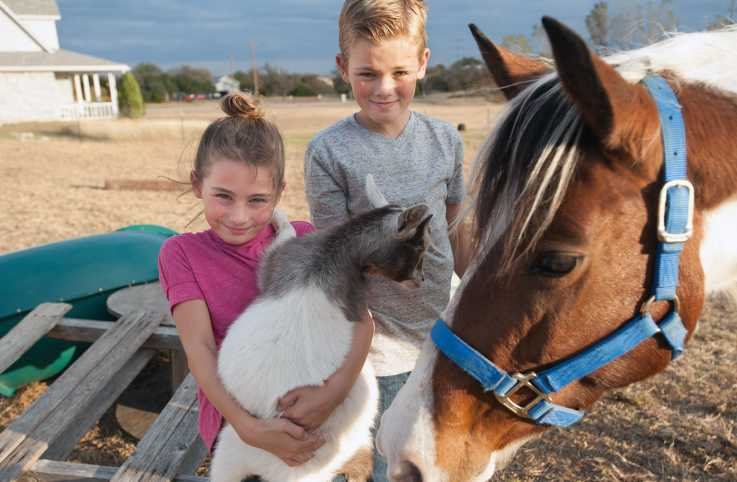 Kamryn (left) and Korbin pose with two of the Hances' rescued animals