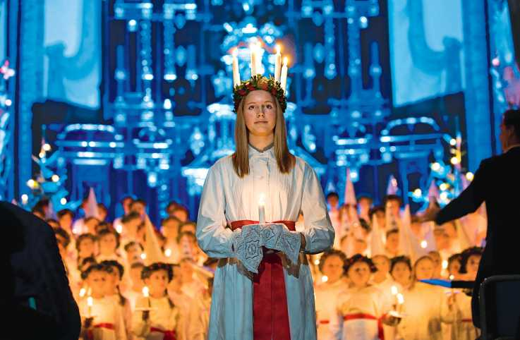 A young Swedish girl in a candlelit crown portrays St. Lucia