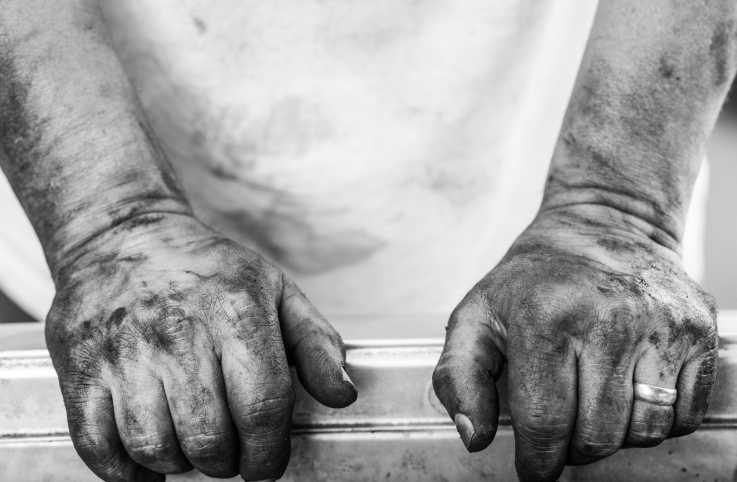 A black and white photograph of tough hands with dirt on them.