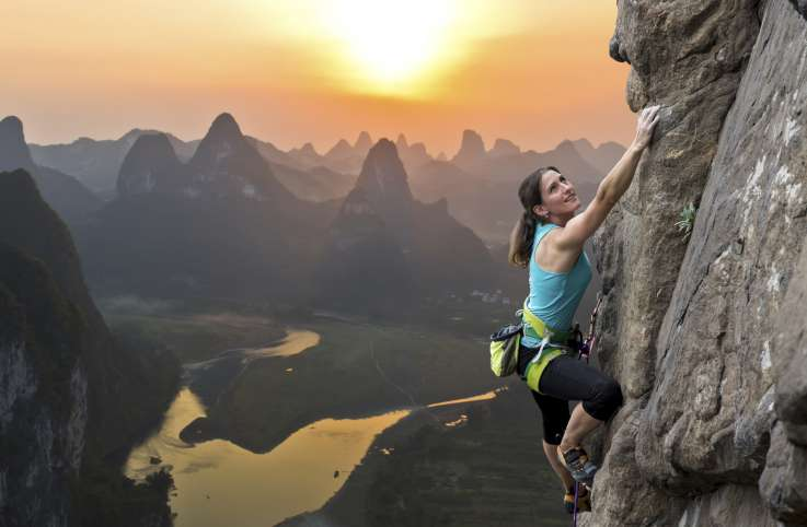 woman climbing a mountain at dawn