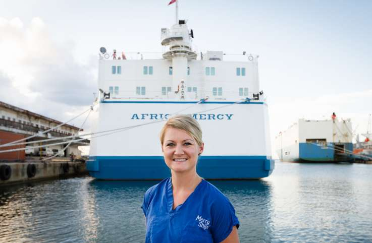 Heather Morehouse poses in front of the ship she served on, Africa Mercy