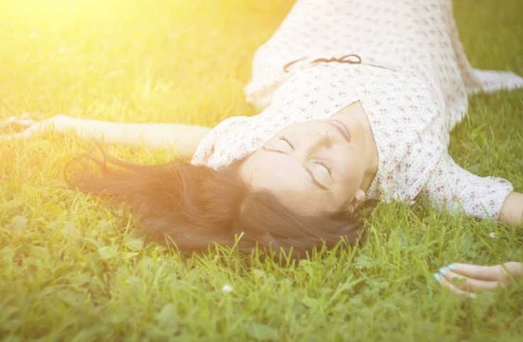 A woman lies in the grass in sunlight getting peace reducing stress