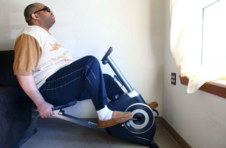Guideposts: Willie exercises on a recumbent stationary bike in his apartment