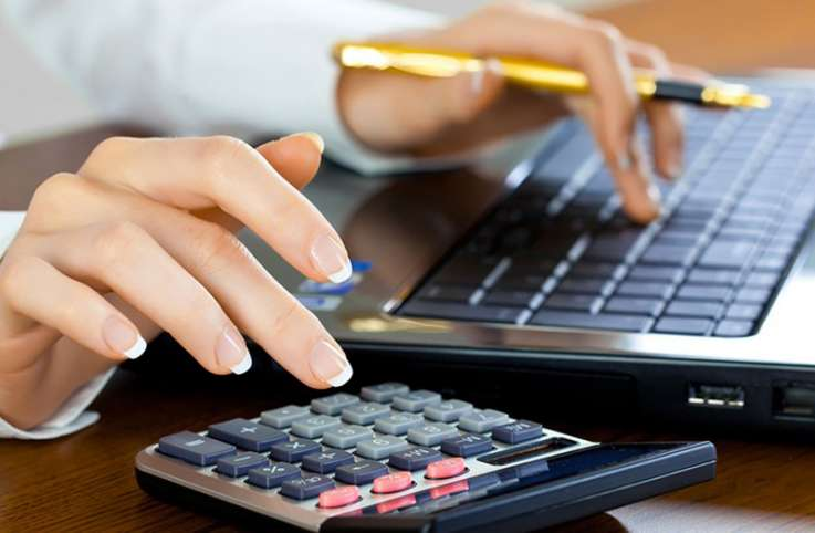 Woman calculating numbers using a calculator