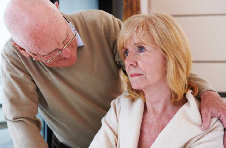 A senior man cares for his wife, who is dealing with Alzheimer's syndrome