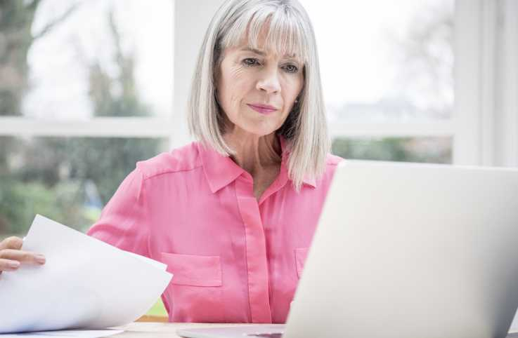 Serious elderly woman looking at her laptop