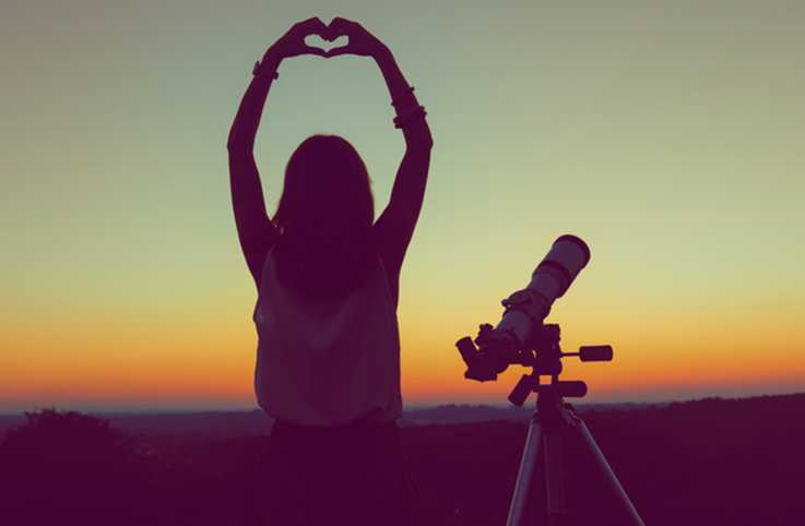 Woman with a telescope putting up a heart symbol