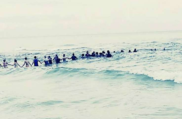 80 person human chain forms to save family on beach