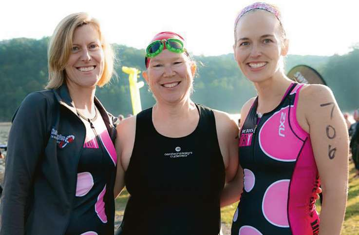 Millie and two friends smile after taking part in a triathlon