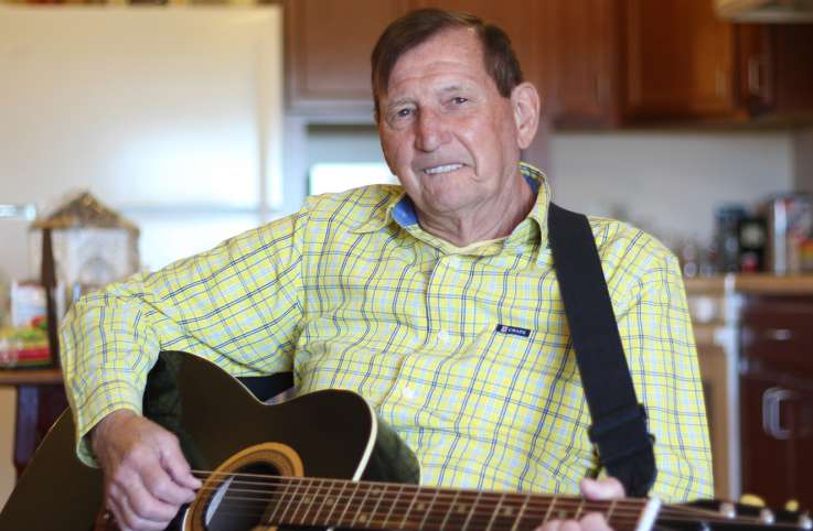 James Carlson in his apartment playing the guitar