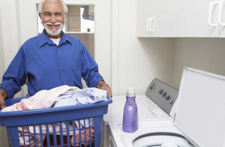 Elderly man with a laundry basket full of clothes.