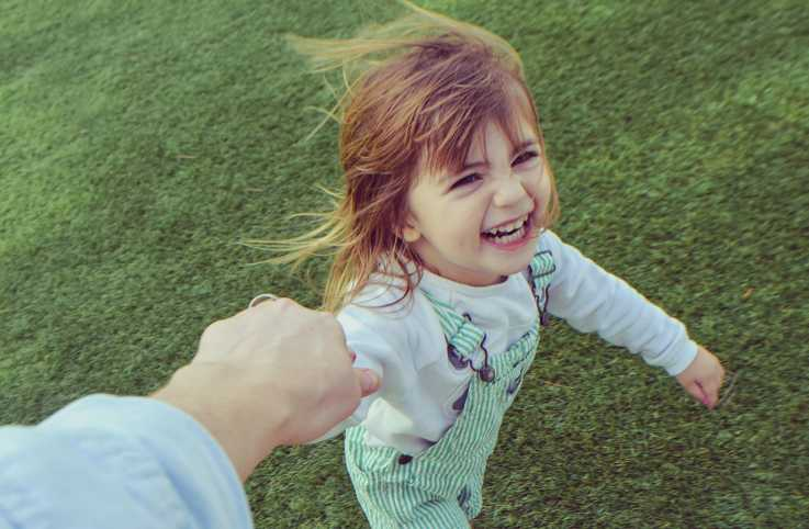 A young girl holding a grownup's hand and laughing