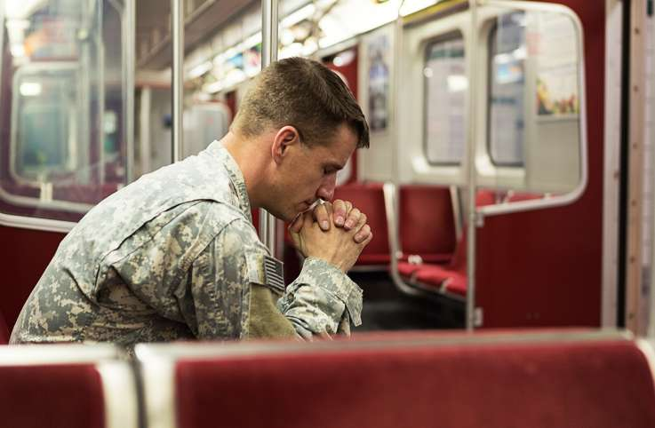 A solider, alone with his thoughts, on a train