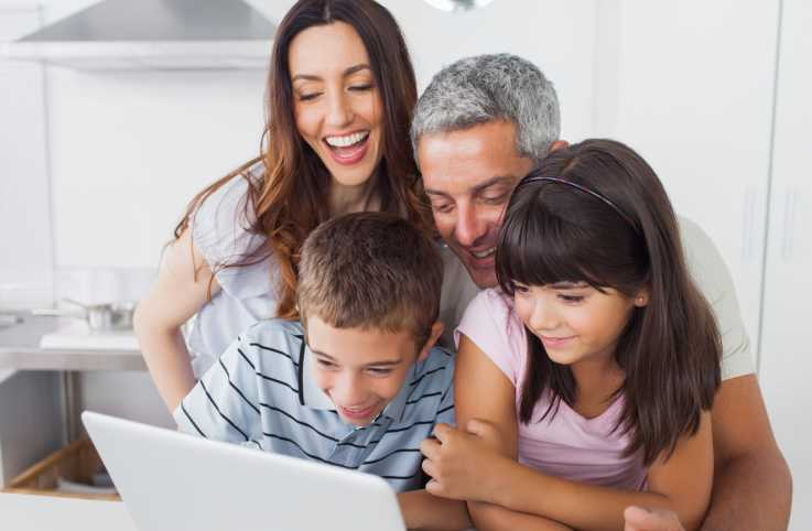 A happy family gathers around a laptop computer to see the new Guideposts website