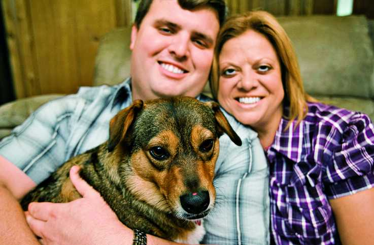 """Carolyn, with son Brandon and Peanut Butter, who """"has become my comfort dog."""""""