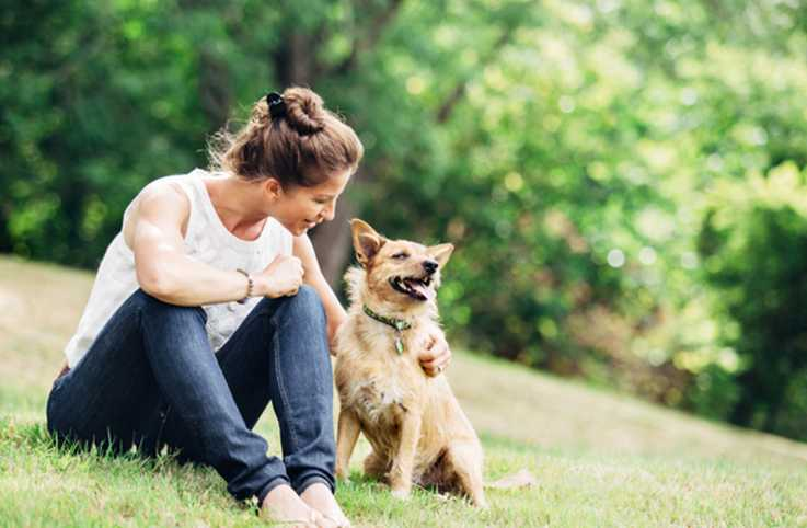 Woman and her dog relaxing on the grass