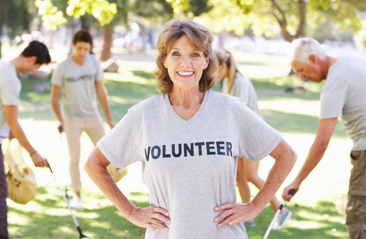 A mature woman pauses during her volunteer activities