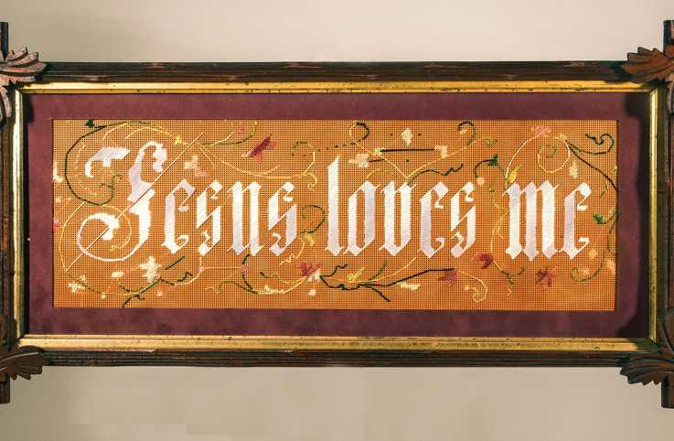 A framed antique sampler that reads, Jesus Loves Me