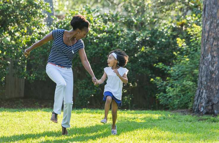 A mother and daughter frolic outside on a sunny day