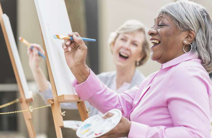 two senior women painting