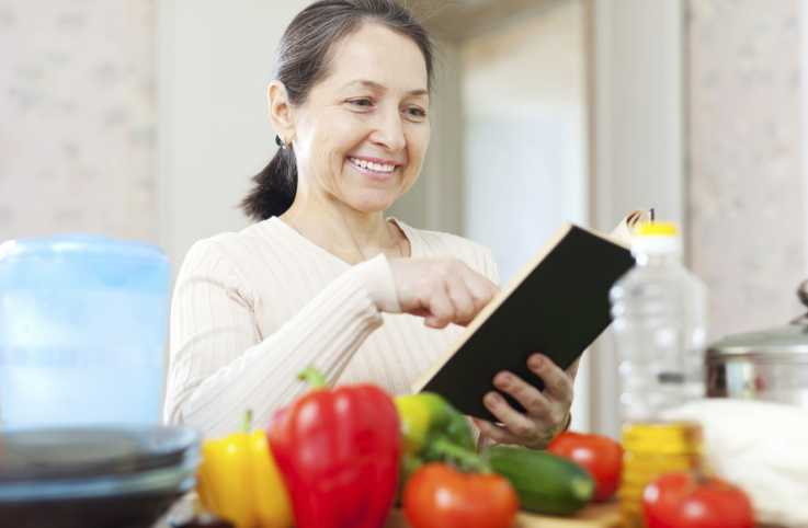 A senior woman in the kitchen consulting her recipe book for a dish.