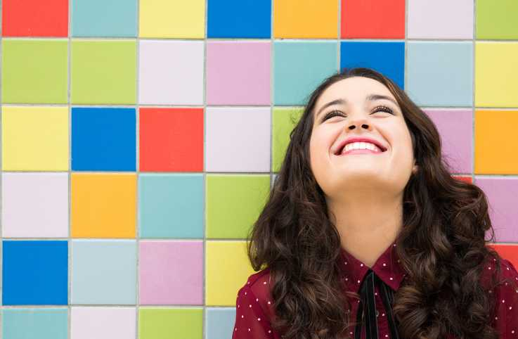 A smiling woman gazes upward, a wall of brightly colored tiles behind her