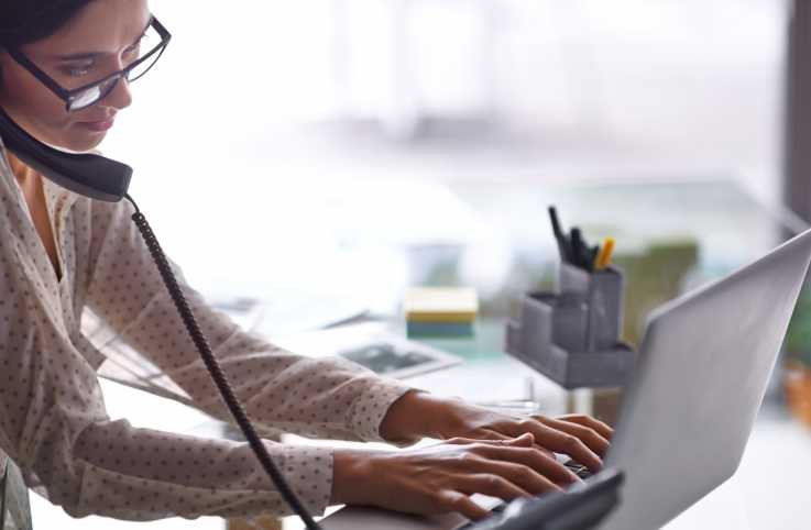 A woman at her office desk on the phone and typing on her laptop.