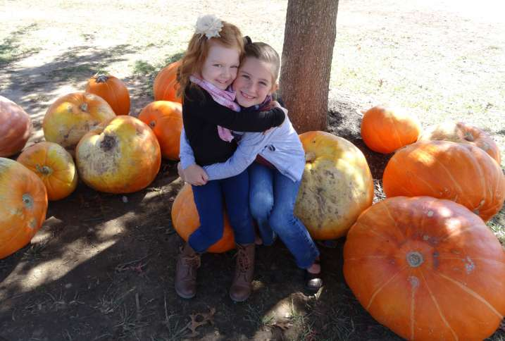 Michelle's granddaughters Ava and Anna pose with a pile of pumpkins.