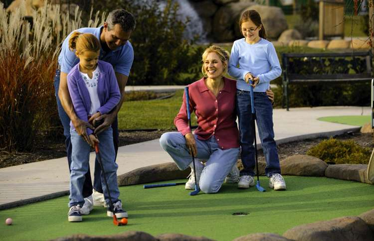 A father shows his daughter how to putt on a mini-golf course as Mom and brother look on.