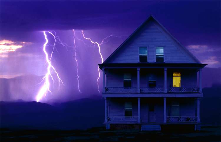 A huge flash of lightning appears behind an inviting rural home, lit from within.