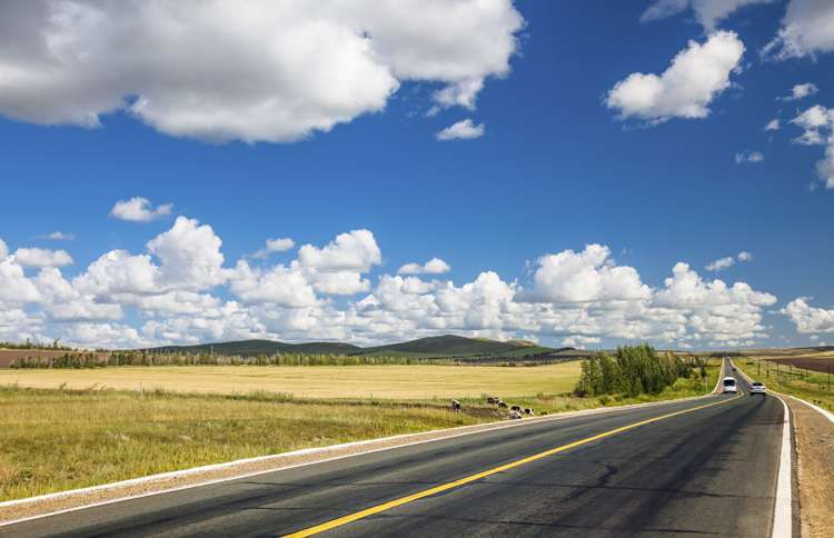 Puffy clouds in a bright blue sky hover over a beckoning highway that stretches into the distance.