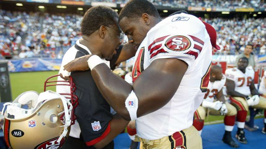 Chaplain Earl Smith prays with Moran Norris during a 2007 road game against the San Diego Chargers.