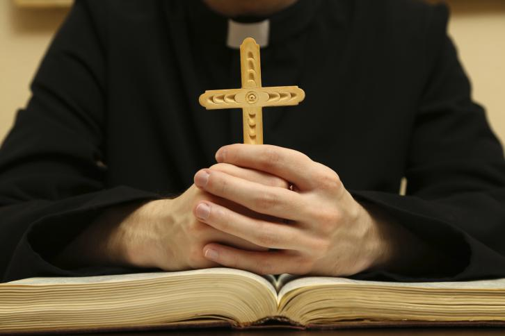 A priest holds a cross over an open Bible