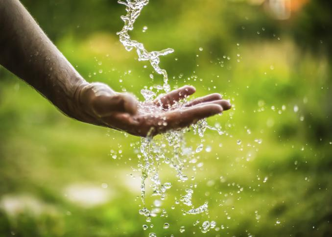 A man sticks his hand into a downward stream of water