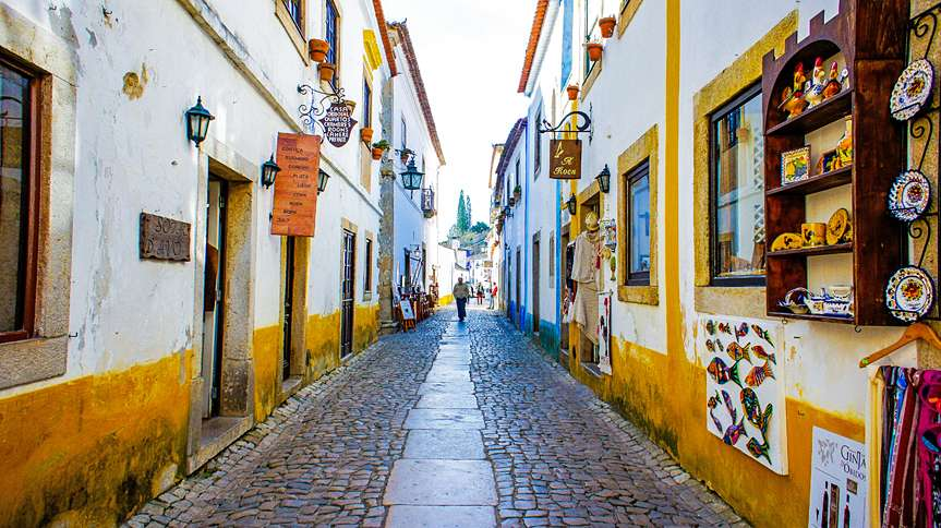In Obidos, whitewashed houses are held in by medieval city walls.