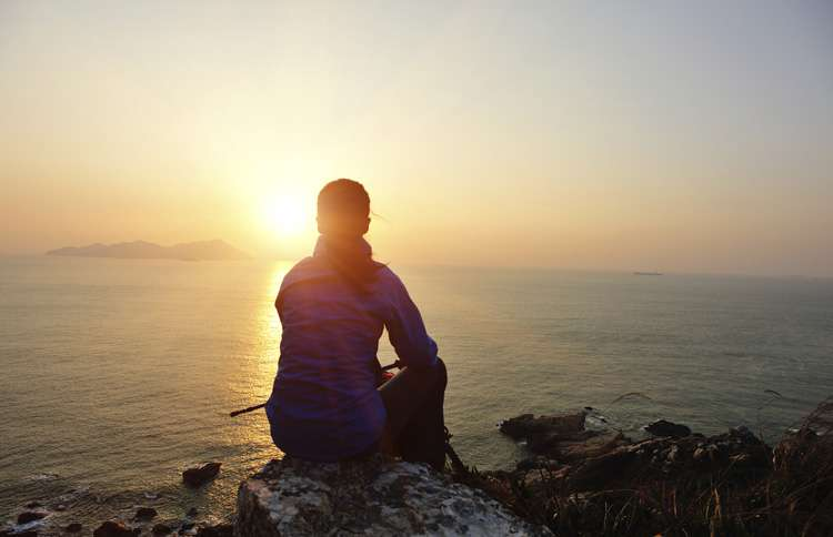Woman sitting on a cliff staring at the sun