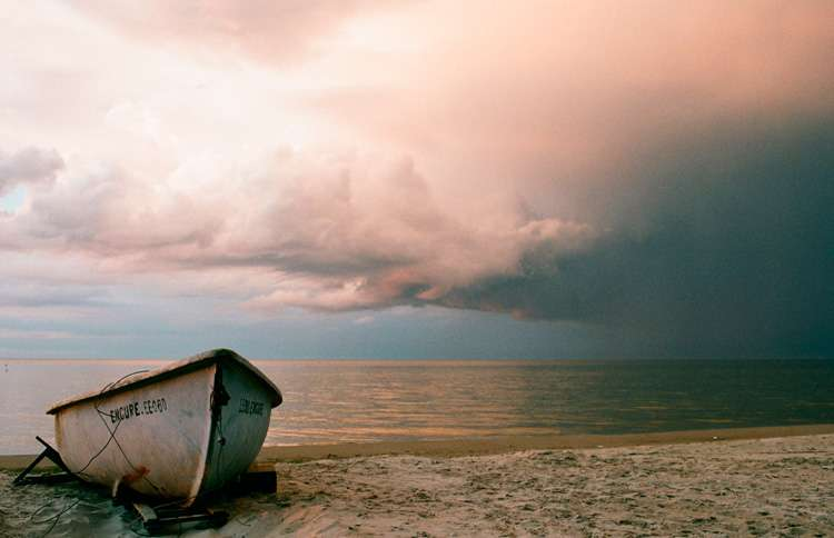 Boat sitting on the beach with a storm approaching