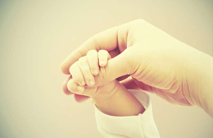 Mother holding baby's hand