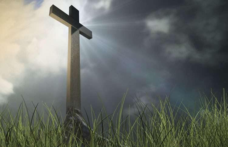The sun shines on a cross in the middle of a field at dawn