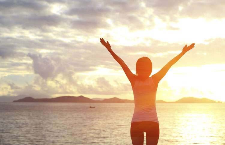 A woman stands on the beach at dawn with her arms raised in praise